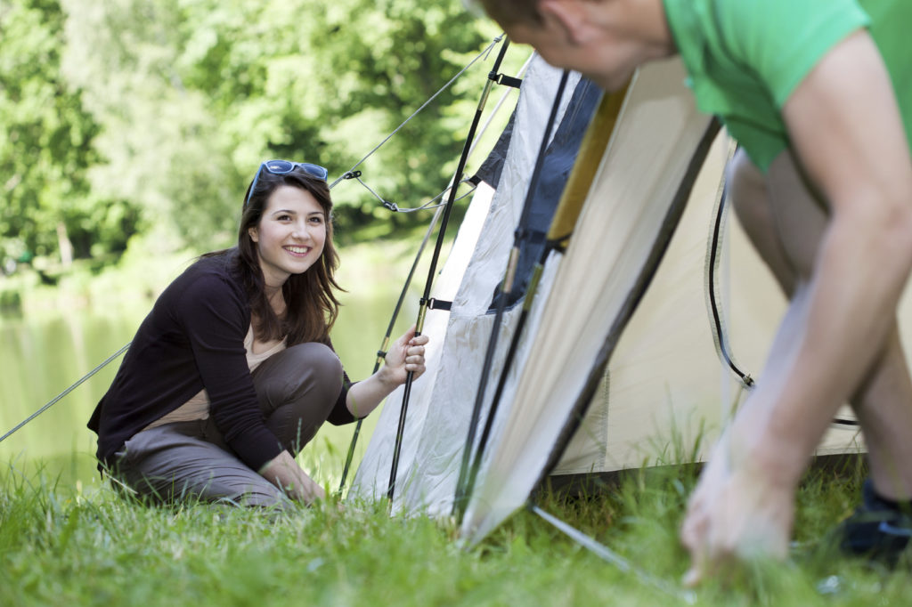 Woman and man pitching a tent together